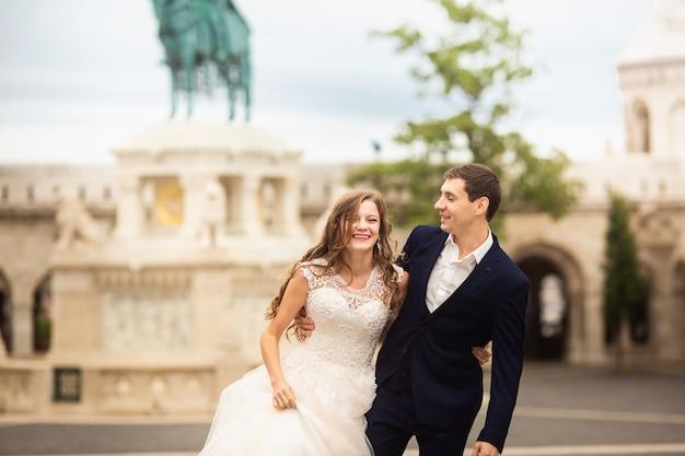 Joven y bella pareja elegante de recién casados caminando por el bastión de los pescadores en budapest, hungría