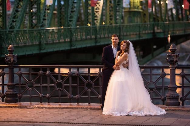 Joven y bella pareja elegante de recién casados cerca del río en budapest