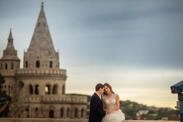 Joven y bella pareja elegante de recién casados sentados junto al bastión de los pescadores en budapest, hungría