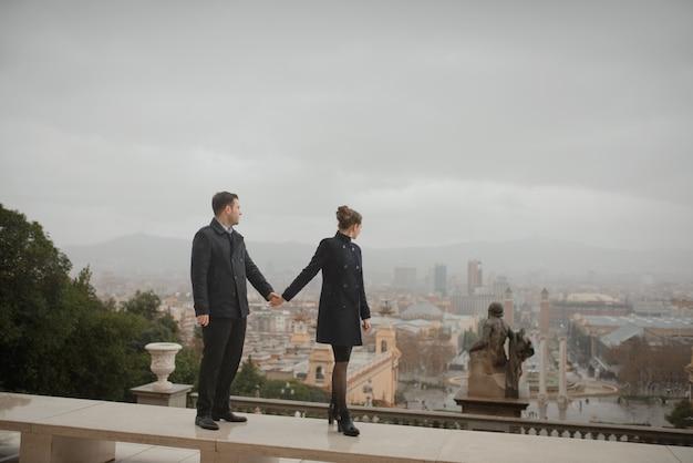 Joven y bella pareja española en el amor se abraza bajo la lluvia frente al museo nacional de arte de cataluña. disparo contra el fondo de la plaza de españa en barcelona.