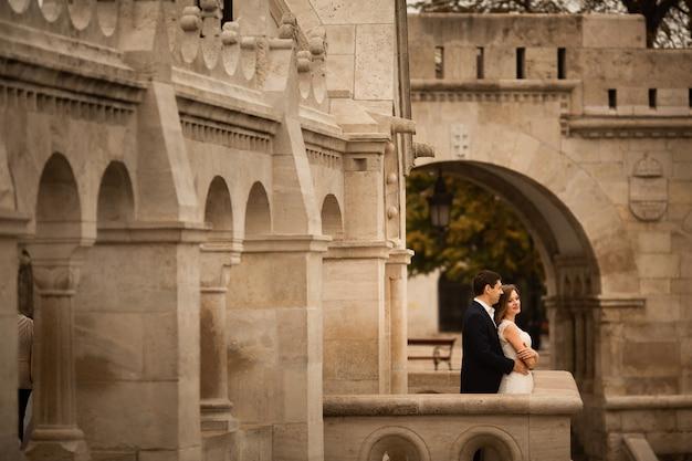 Joven y bella pareja de recién casados con estilo abrazando por el bastión de los pescadores en budapest, hungría