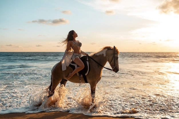 Joven belleza morena divirtiéndose con caballo y montando playa tropical