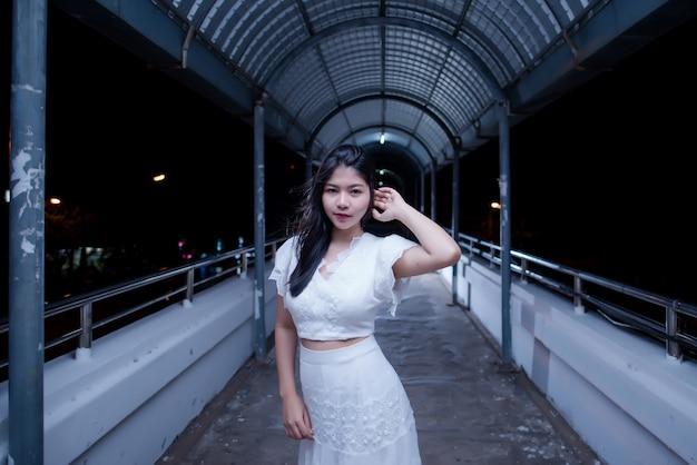 Joven belleza mujer en vestido blanco de luz de noche