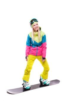 Joven belleza en traje de esquí y gafas de esquí en snowboard