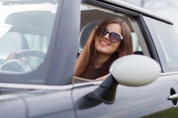 Joven beuatiful mujer conduciendo un automóvil