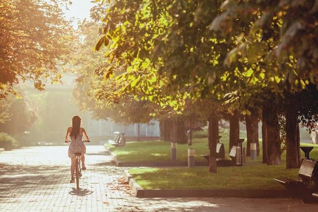 La joven con bicicleta en el parque