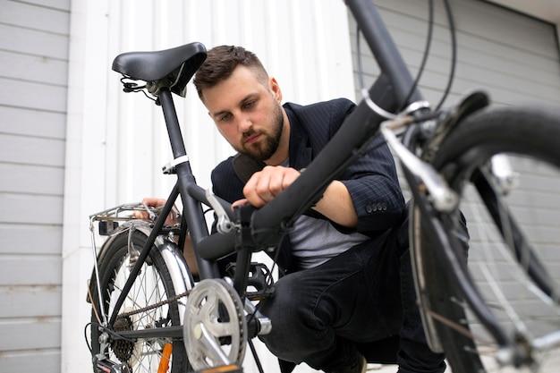 Joven con una bicicleta plegable en la ciudad