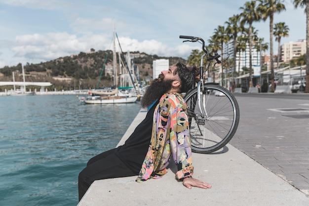 Joven con bicicleta sentado cerca de la costa relajante