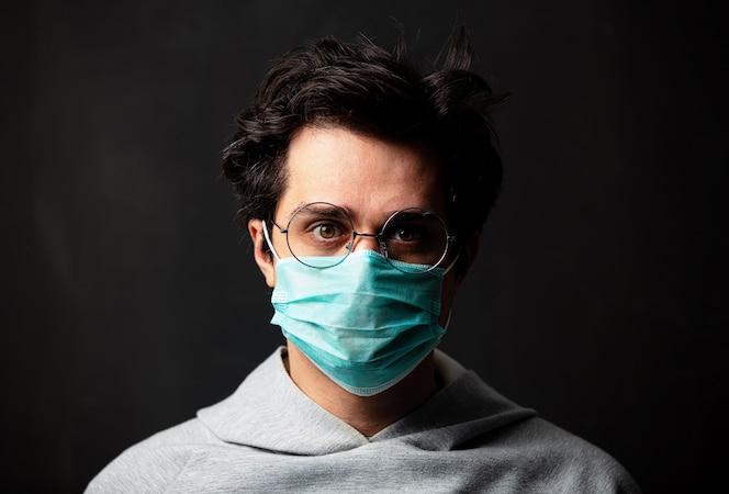 Joven blanco con gafas y máscara protectora