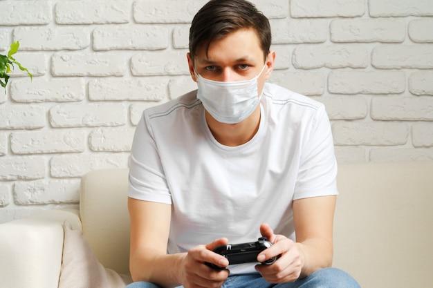Joven blanco jugando videojuegos con máscara médica en la cara mientras covid-19 está en cuarentena