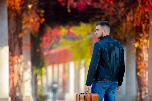 Joven blanco con maleta en callejón de uva roja