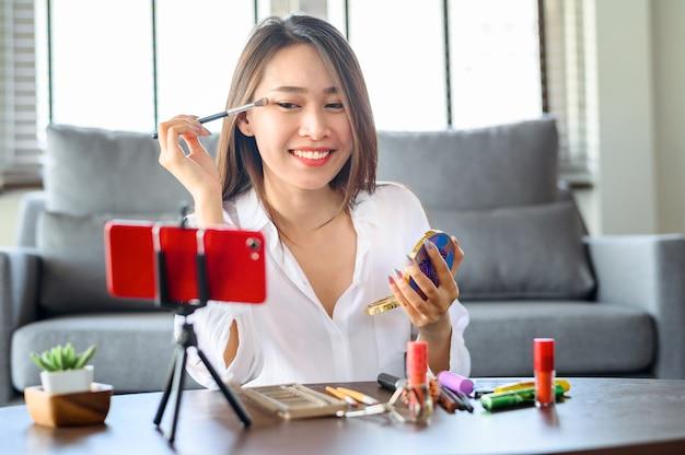 Joven blogger asiática influencer mujer grabando video maquillaje cosmético en casa