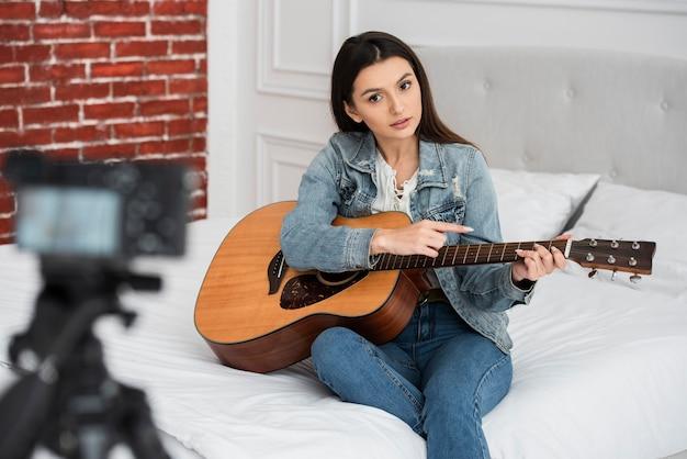 Joven blogger enseñando a tocar la guitarra