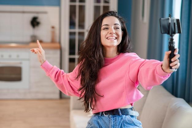 Joven blogger feliz usando selfie stick y hablando por teléfono