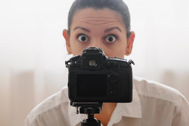 Joven blogger femenina con cámara.