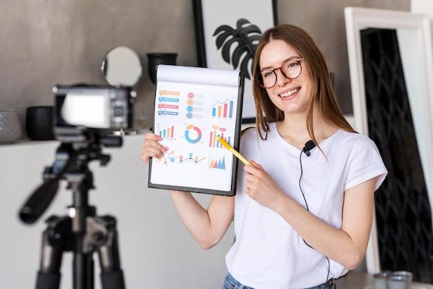 Joven blogger grabando con cámara profesional con portapapeles con gráficos