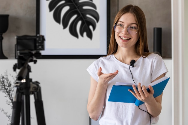 Joven blogger grabando con cámara profesional sosteniendo un libro