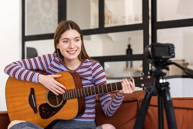 Joven blogger grabando a sí misma sosteniendo la guitarra