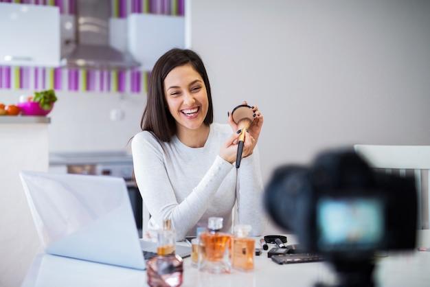 Joven blogger linda mujer filmando su presentación de productos cosméticos. sentado en una habitación luminosa frente a la cámara.