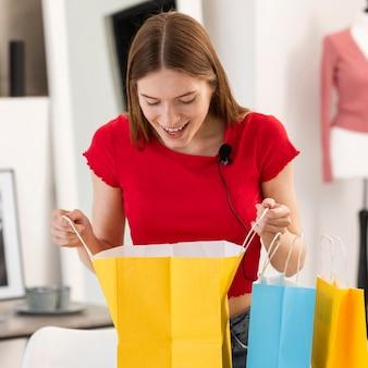 Joven blogger mirando dentro de la bolsa de compras