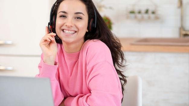 Joven blogger sonriente con auriculares y portátil