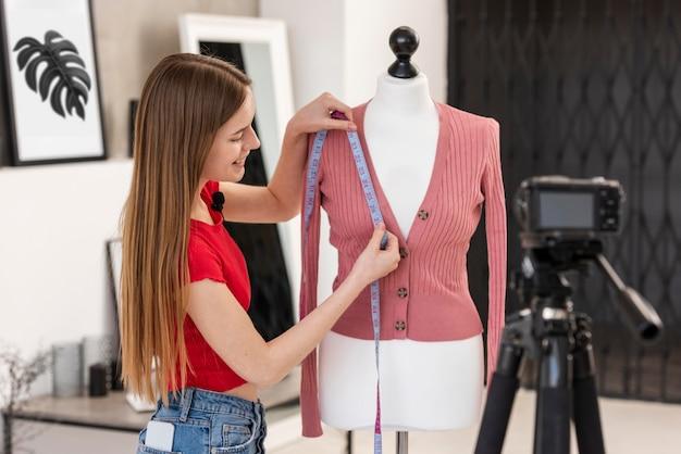 Joven blogger tomando medidas de ropa