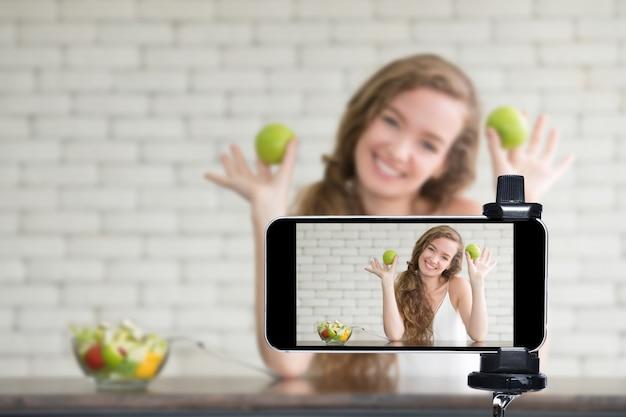 Joven blogger y vlogger e influyente en línea transmitiendo en vivo un programa de cocina en las redes sociales usando un teléfono inteligente