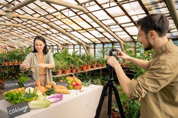 Joven bloguera asiática que usa un teléfono inteligente y presenta una nueva aplicación para controlar la ración orgánica mientras su novio graba una revisión de video en la cámara