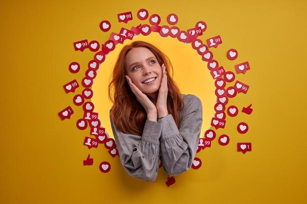 La joven bloguera está feliz de obtener muchos me gusta y opiniones, se para entre los botones de signos de corazón, emocionada y alegre, sonriendo. retrato