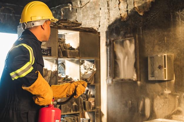Joven bombero asiático, los bomberos utilizan extinción de incendios que se están quemando en el edificio.