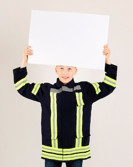 Joven bombero sosteniendo pancarta en blanco