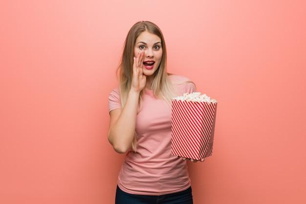 Joven bonita chica rusa gritando algo feliz al frente. ella está sosteniendo palomitas de maíz.