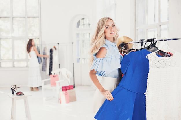 La joven bonita eligiendo y probándose vestidos en la tienda