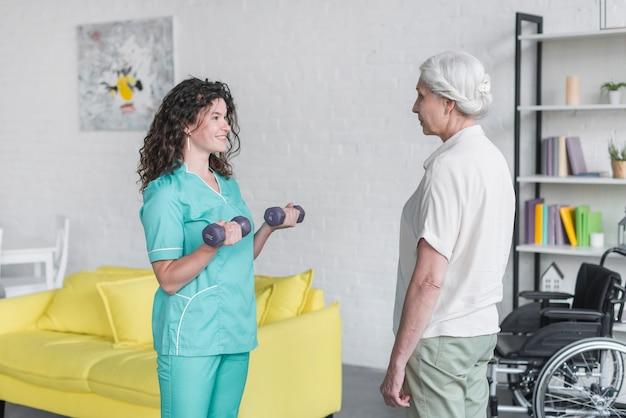 Joven bonita enfermera ayudar a anciana en su terapia con pesas