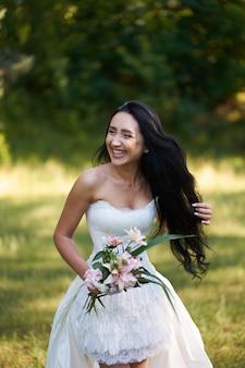 Joven bonita morena mujer riendo en vestido de novia blanco, caminando al aire libre