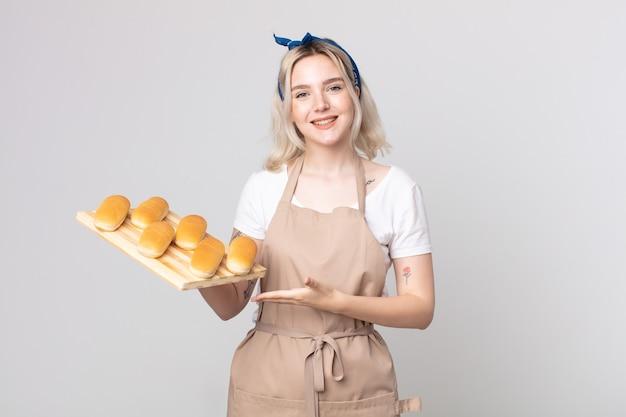 Joven y bonita mujer albina sonriendo alegremente, sintiéndose feliz y mostrando un concepto con una bandeja de bollos de pan