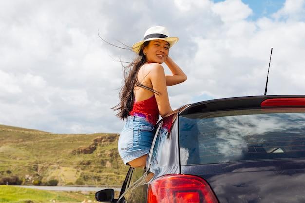 Joven bonita mujer asiática amante de la vida fuera de la ventana del coche