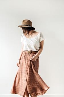 Joven bonita a mujer bailando en falda larga, sombrero, blusa blanca sobre blanco