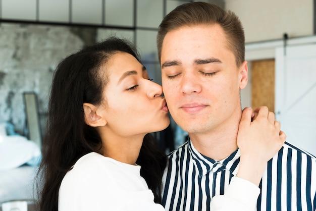 Joven bonita mujer besando a novio en la mejilla