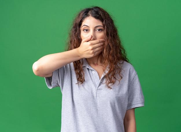 Joven bonita a mujer caucásica cubriendo la boca con la mano