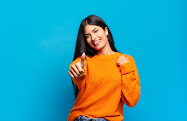 Joven bonita a mujer hispana que se siente orgullosa, despreocupada, segura y feliz, sonriendo positivamente con los pulgares hacia arriba