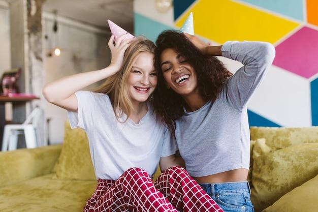 Joven bonita a mujer sonriente con cabello rubio y mujer afroamericana con cabello oscuro y rizado en gorras de cumpleaños felizmente mientras pasa tiempo junto con la pared colorida