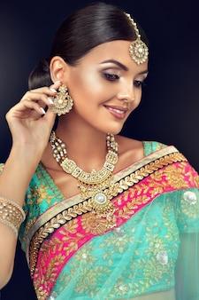 Joven bonita a mujer vestida con un maquillaje exquisito y traje nacional indio con elegante conjunto de joyas
