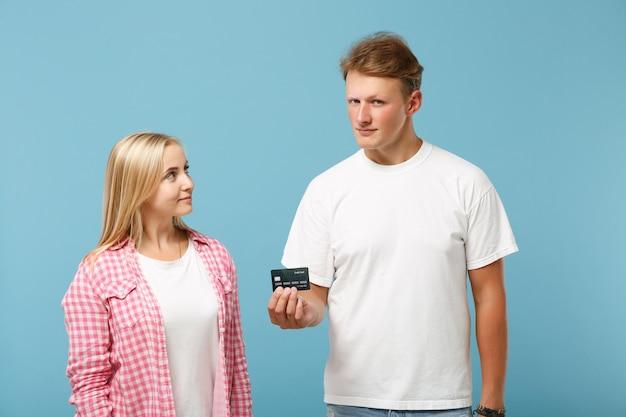 Joven bonita pareja dos amigos chico y mujer en blanco rosa camisetas en blanco vacías posando