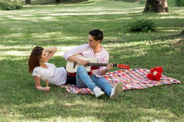 Joven bonita pareja haciendo un picnic en el parque