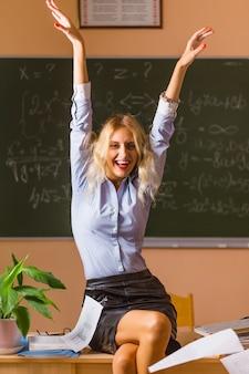 Joven bonita profesora gritando en el aula