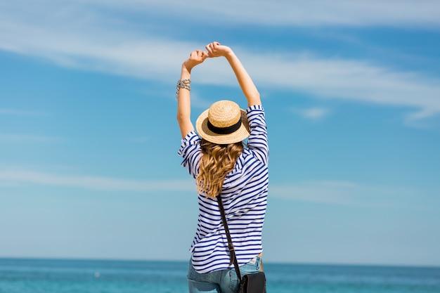 Joven bonita rubia bronceada joven de pie en la playa cerca del mar esperando y soñando