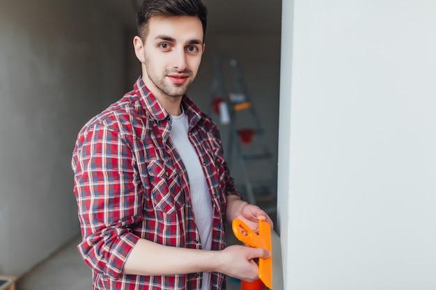 Joven bonito hombre con espátula en las manos, haciendo reparaciones