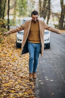 Joven en el bosque con abrigo en el coche