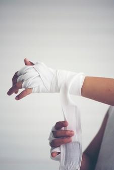 Joven boxeador envolviendo las manos con envolturas de boxeo